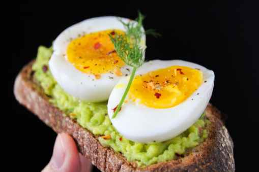 sliced egg on top of green salad with bread